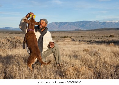 Casual African American man playing with his dog outdoors