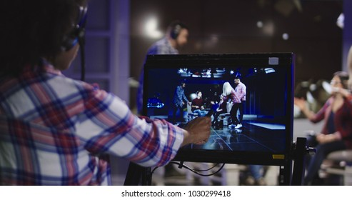 Casual African-American woman in headset controlling process of shooting TV show standing in front of computer screen and watching record.