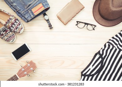 Casual apparel and accessories on a background of wood.
