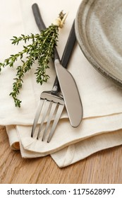 Casual artisanal table setting place setting with wrought iron fork and knife silverware, stoneware pottery plate, white linen cloth napkin and a sprig of fresh thyme herbs on rustic wood tabletop