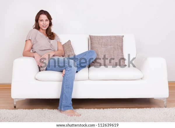 Casual barefoot woman in jeans sitting on a couch in her living room with a cheerful smile
