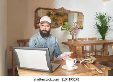 Casual bearded man in cap using laptop at table with served breakfast and holding notepad