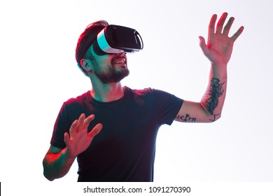 Casual bearded man with tattoo trying VR headset and exploring another world isolated on white.