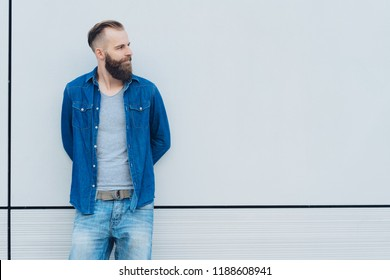 Casual bearded man watching to the side looking towards blank copy space on a white exterior wall