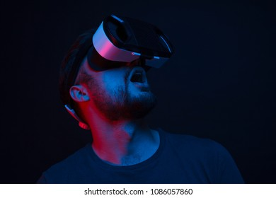 Casual bearded man wearing goggles of virtual reality and looking up in excitement standing in neon lights.