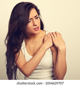Casual beautiful woman with muscle pain in shoulder holding the hands with suffering face on white background