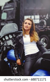 Casual beautiful woman sits on a big tourist motorcycle on the street bright smile on a sunny day.