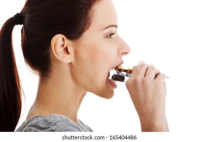 Casual beautiful woman trying to eat blister of pills. Isolated on white.