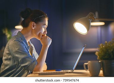 Casual beautiful woman working on a laptop at the night at home.