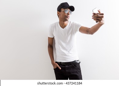 Casual black guy in shades and cap taking selfie with smart phone on light background with copy space
