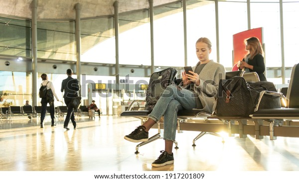 Casual blond young woman talking on cell phone while waiting to board a plane at airport departure gates.
