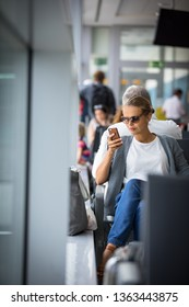 Casual blond young woman using her cell phone while waiting to board a plane at departure gates at international airport.