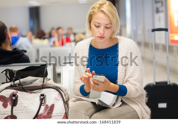 Casual blond young woman using her cell phone while waiting to board a plane at the departure gates.
