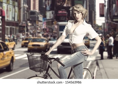 casual blonde girl with casual style wearing jeans and shirt  in sensual pose near bicycle