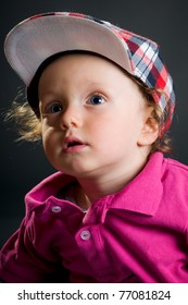 casual boy with cap in studio on gray ground