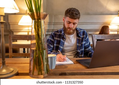 Casual business man or freelancer planning his work on notebook, working on laptop computer with smart phone, cup of coffee on table at coffee shop or home office.