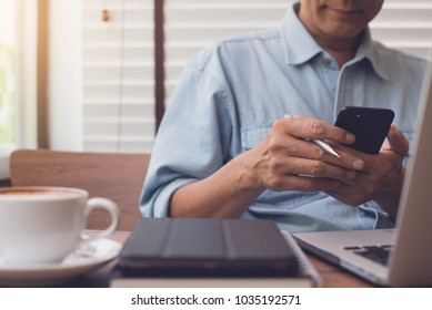 Casual business man or freelancer using mobile smart phone, working on laptop computer with book, notebook and cup of coffee on table at coffee shop or home office, working from cafe concept, close up