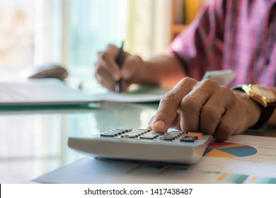 Casual business man hand using calculator and signing chequebook, work on computer notebook, data graph peperwork and wireless mouse on the table at workplace.
