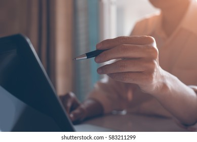 Casual business man holding a pen and busy working on laptop computer in office, backlit, overtime working, e business concept