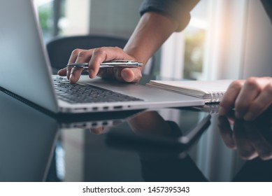 Casual business man with pen in hand busy working on laptop computer, typing on keyboard with notebook, mobile smart phone on desk in modern office, close up, dark tone