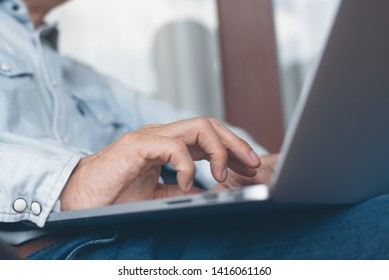 Casual business man relax working from home browsing internet on laptop computer. Freelancer, blogger typing on laptop computer keyboard, online working concept, close up. Man networking at home