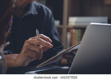 Casual business man using digital tablet while working on laptop computer in office. Freelancer, Creative designer working on web design project on tablet pc, close up. Business and technology concept