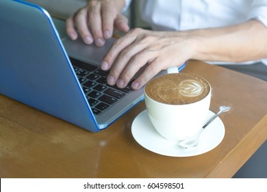 Casual Business man using multichannel services on laptop computer in vintage coffee shop.City lifestyle business man hands working on typing keyboard using  4G 5G wifi internet online communication