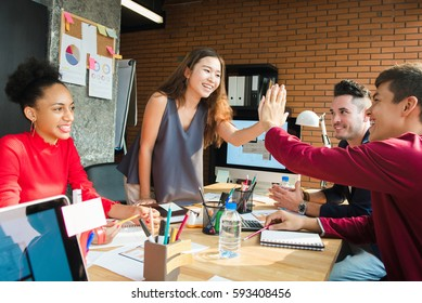 Casual business people making high five in the meeting - business celebration concept