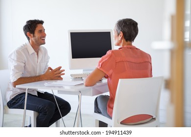 Casual business people talking at desk and smiling in the office