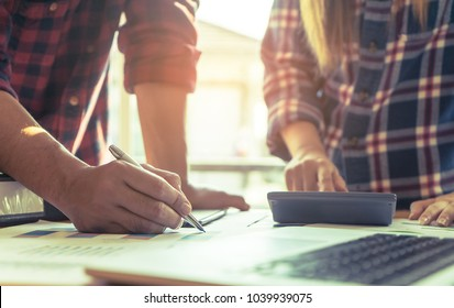Casual business team writing and caulcualting financial report