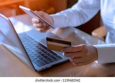 Casual  business woman hands  holding golden credit card  using mobile phone for online shopping and payment  with laptop computer on the table at home office. Digital banking and e commerce concept
