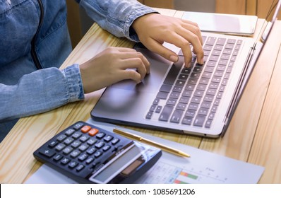 Casual business woman working on labtop computer, analyzing about data project, with calculator,  pen  and documentary graph paper on the wooden table .