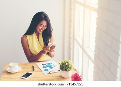 Casual business women are counting money happily  from selling products online by phone with business documents on the table in the cafe