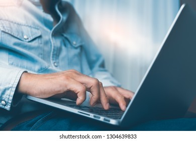 Casual businessman, freelancer working from home browsing internet on laptop computer. Man typing on laptop computer keyboard, close up, online working concept. vintage tone