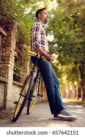 Casual businessman going to work by bicycle. He is standing next to bike and thinking.