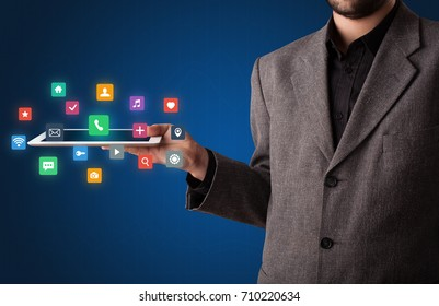 Casual businessman holding tablet with colorful applications