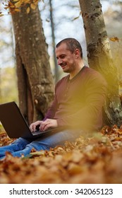 Casual businessman with a laptop working outdoor in a forest, mobility concept