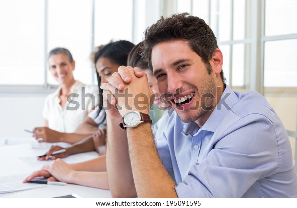 Casual businessman laughing during meeting in the office