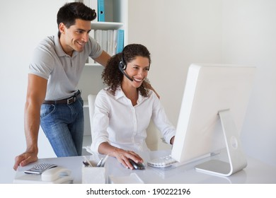 Casual businessman looking at colleagues computer in the office