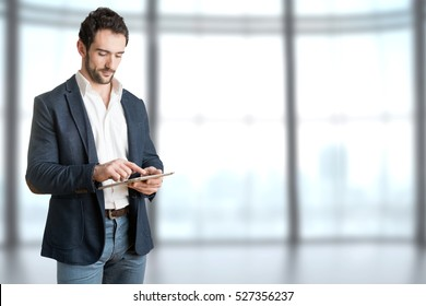 Casual Businessman Looking at a tablet, in an office