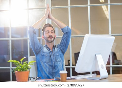 Casual businessman meditating at his desk in the office