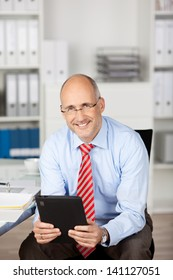 Casual businessman sitting and holding tablet computer in the office