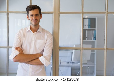 Casual businessman smiling at camera in the office