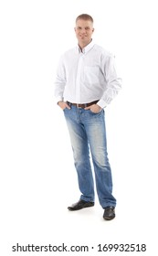 Casual businessman standing with hands in pocket, smiling at camera, cutout, full size.