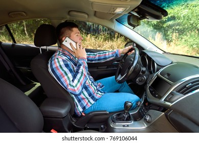 Casual businessman talking on cell phone while driving a car. Handsome young man in plaid shirt talking on mobile phone and smiling while holding steering wheel