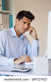 Casual businessman talking on the telephone in his office