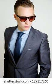 Casual Businessman wearing a stylish suit on a white background wearing sunglasses looking cool