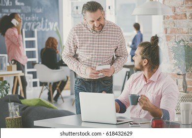 Casual businessman at work, talking with coworker