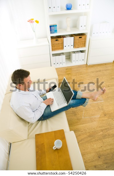 Casual businessman working at home sitting on couch, using laptop computer and mobile phone. High-angle shot.