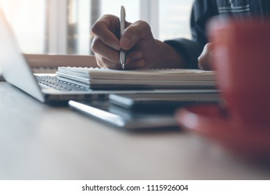 Casual businessman writing on notepad, working on laptop computer with smart phone, coffee cup on desk at home office. Man studying online course from Elearning website, E learning concept close up
